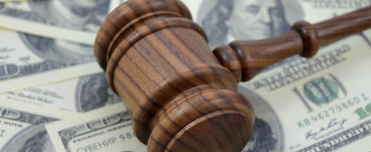 An image focused on the legal side of monetary gains using a gavel and an abundance of American cash as a background.