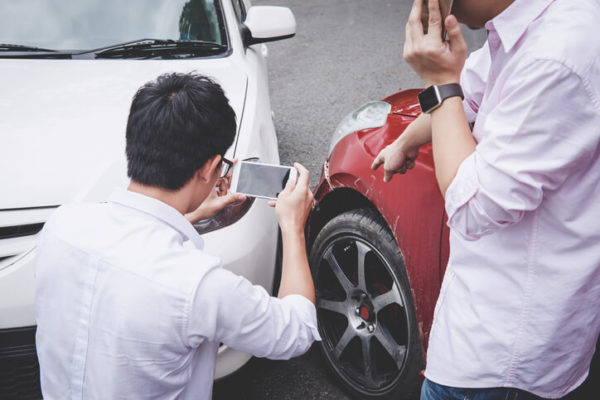 two men evaluating the damage of their cars after a car accident in miami