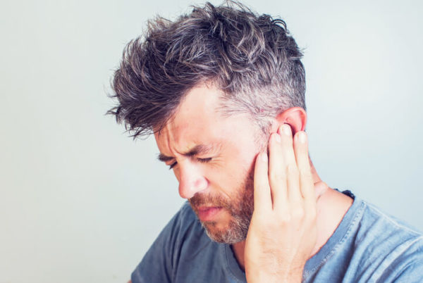man grimacing with ear pain