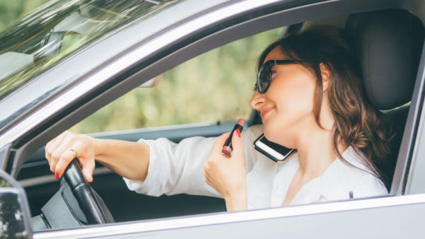 distracted driver talking on the phone and putting on lipstick