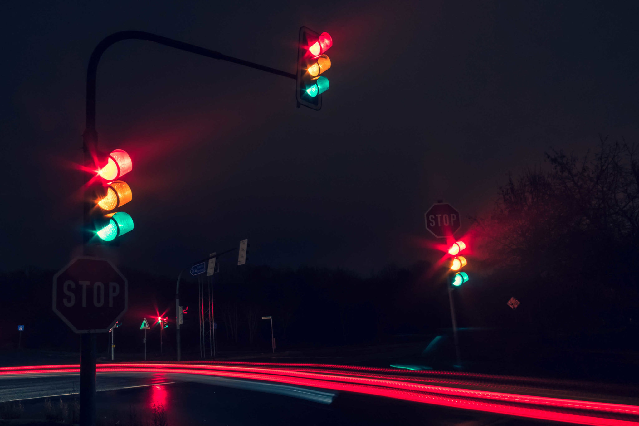 traffic lights at night with lots of traffic zooming past.