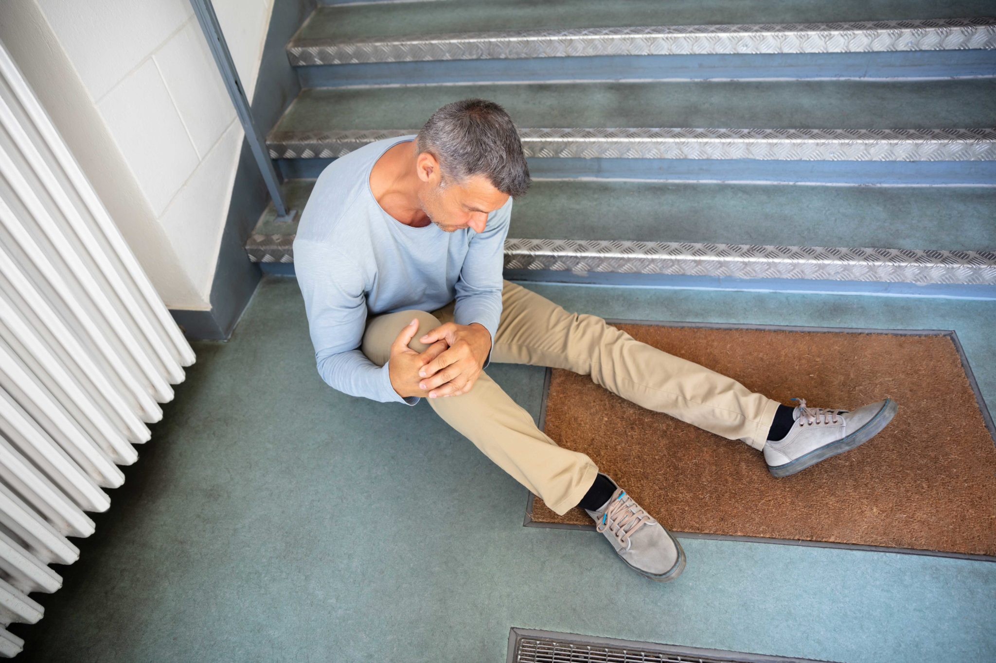 Older man slip and fall on a stair case holding his knee